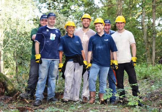Team Wates in yellow caps and blue tshirts in the woods