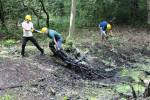 volunteers dragging logs and rubbish from the pond